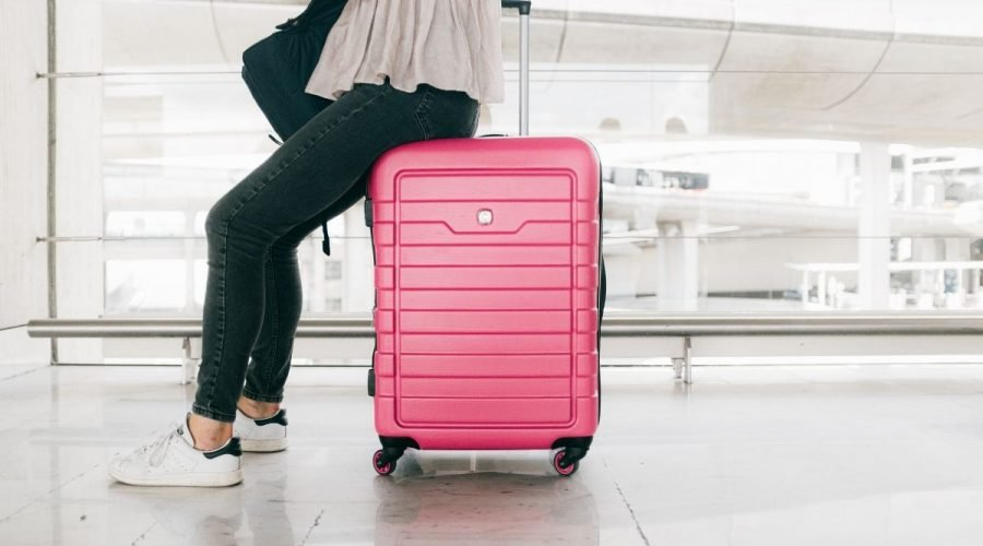 Picture of a lady sitting on a pink carry on suitcase.