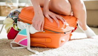 picture of a girl overstuffing her carry on