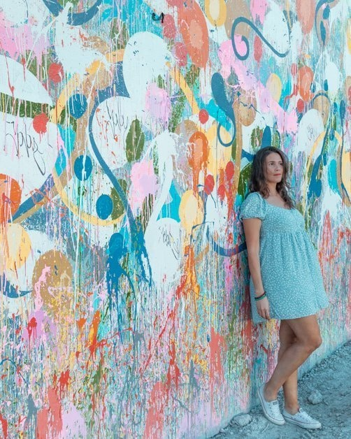 Standing in front of a colorful mural in Wynwood