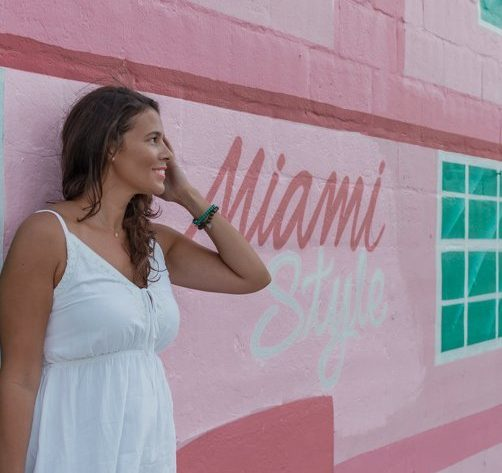Me posing in front of a colorful wall outside of club Space one of the best places to take pictures in Miami.