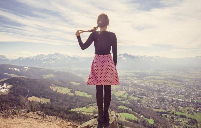 Traveling along quotes image of a girl on a mountain