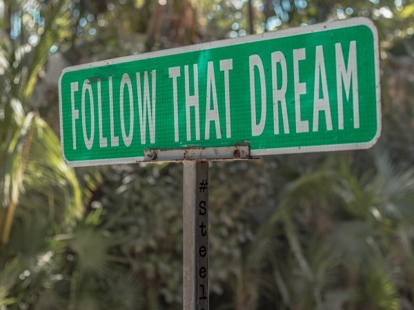 Street sign in Tulum that says follow that dream