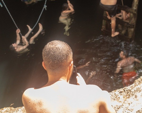 Man looking into Cenote calavera and below a crowd of people swimming