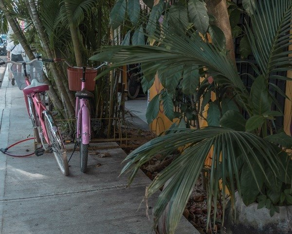 Colorful pink beach cruisers parked outside of a yellow building in Tulum town.