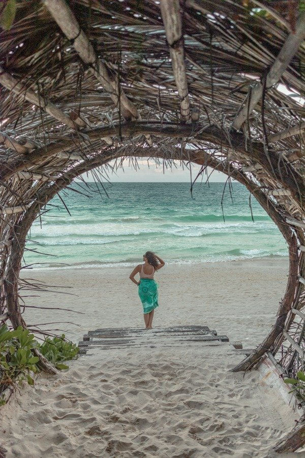 Looking at the beach in front of a wooden tunnel