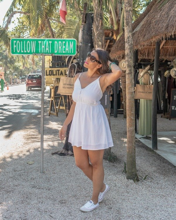 posing at the follow that dream sign one of the popular Tulum Instagram spots.
