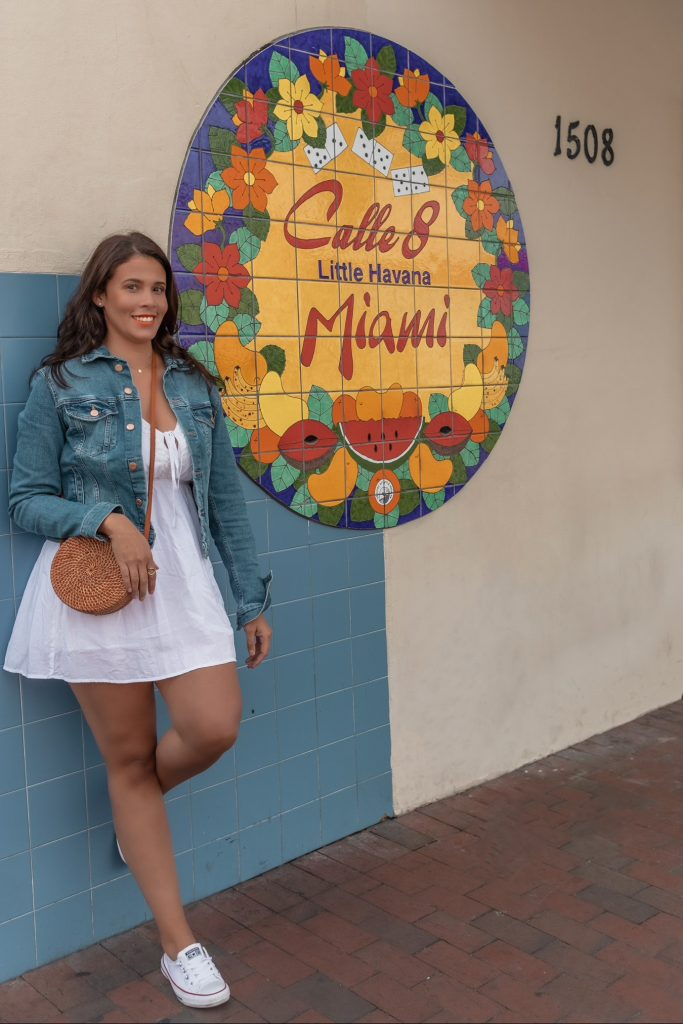 """Posing in front of a popular sign in Miami that says """"Calle 8 Miami Little Havana."""""""