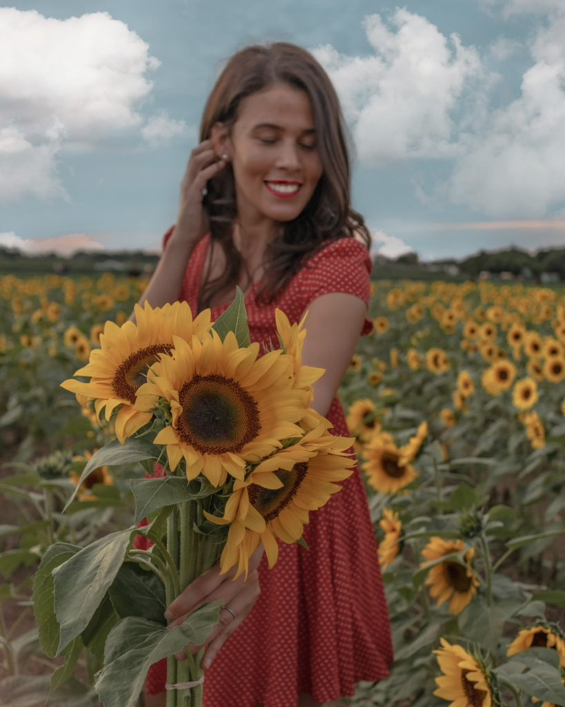 Smiling while holding a bouquet of sunflowers on a sunny day at The Berry Farms sunflower field