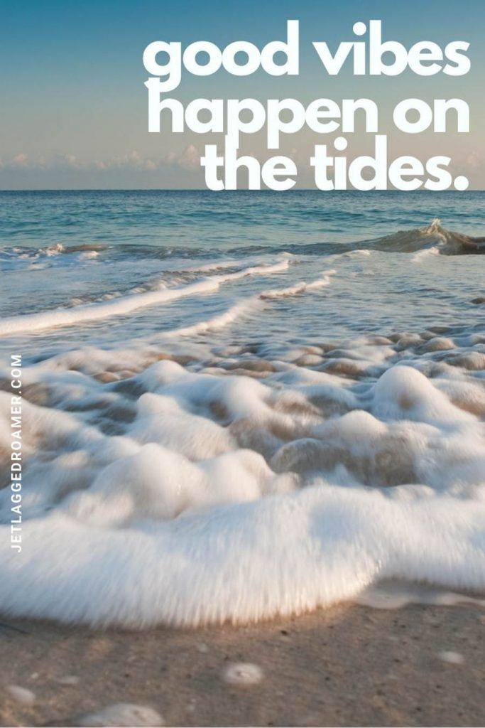 """Foamy shoreline on a sunny day and a quote """"good vibes happen on the tides."""""""