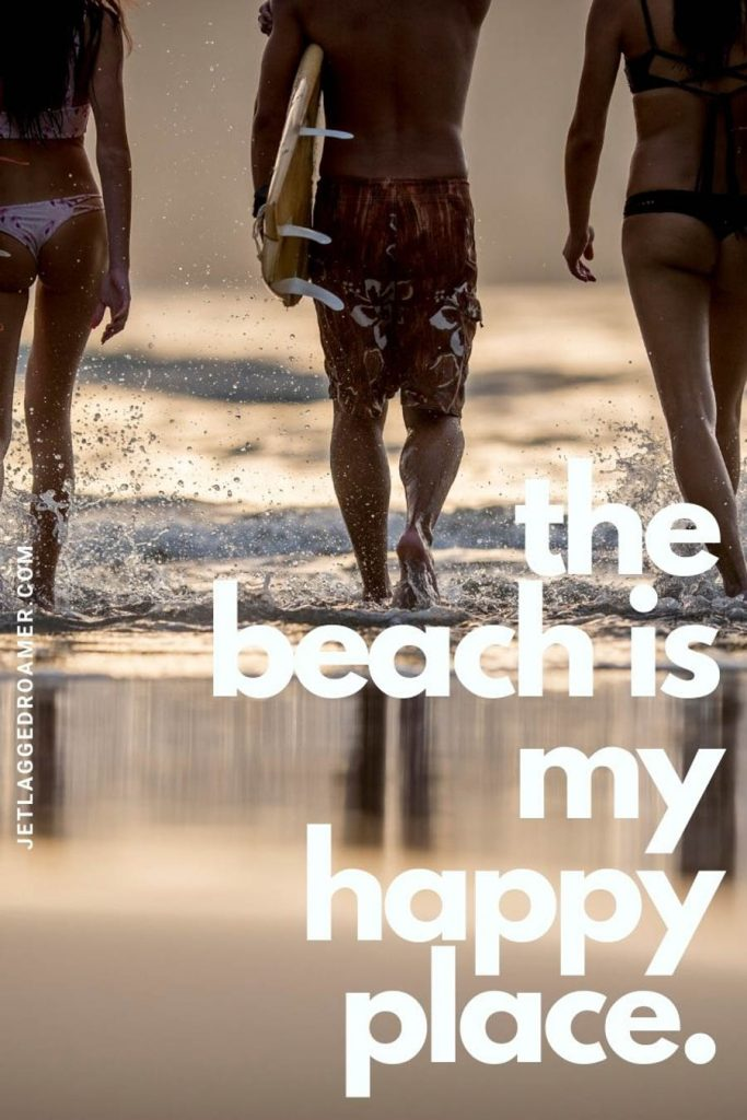 """3 friends walking into the ocean to surf during sunset and a quote that says """"the beach is my happy place."""""""
