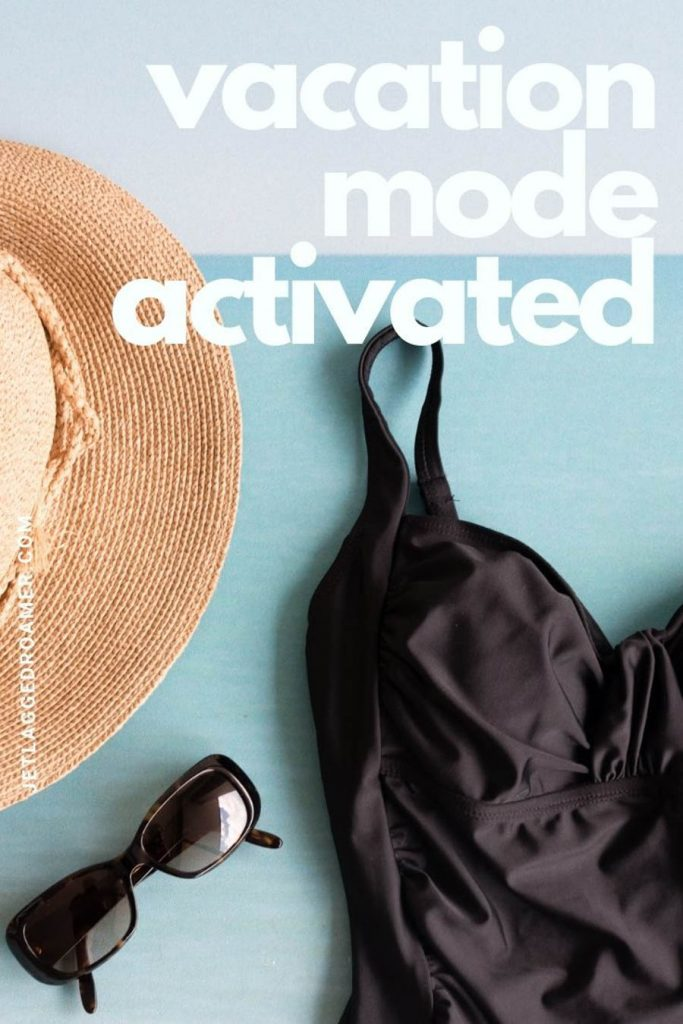 """Black swimsuit next to a straw hat and sunglasses with the quote """"vacation mode activated."""""""