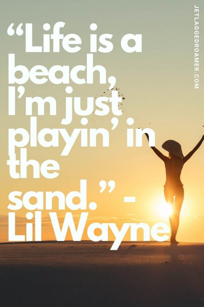 """Girl posing in front of a sunset and a famous beach quote that reads """"life is a beach, I'm just playin' in the sand."""" by Lil Wayne."""