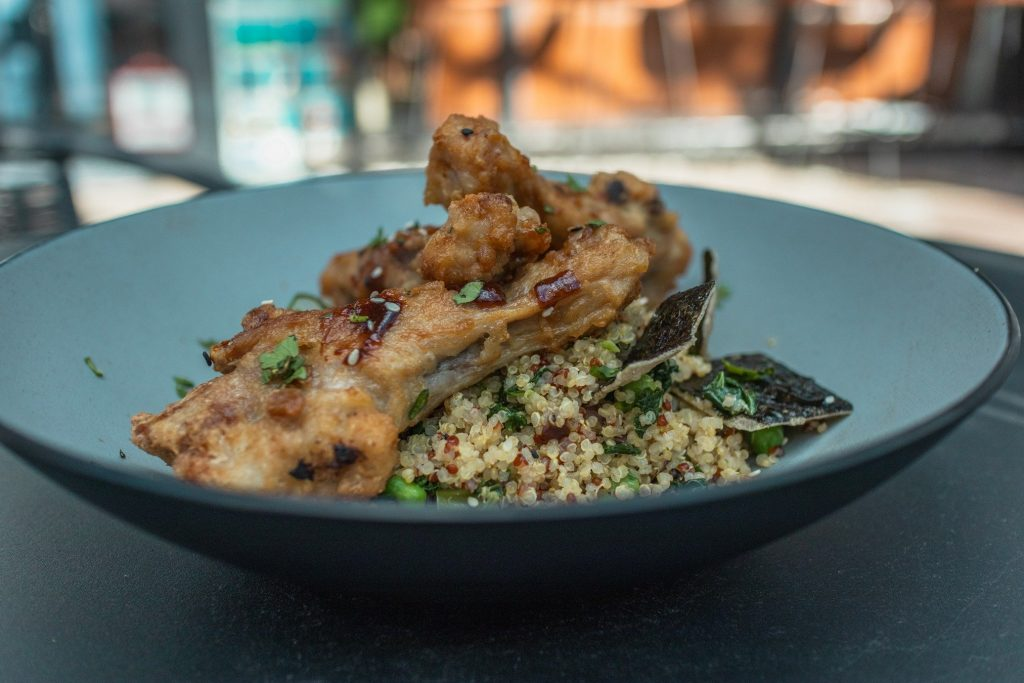 Borsalino duck wings plated and on a table.