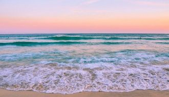 beach quotes and beach captions picture of a beautiful beach during sunset and hues of pinks and oranges over a turquoise beach.