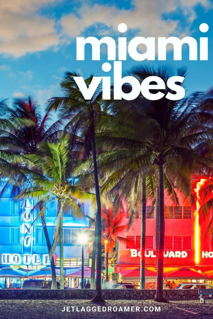 """Beautiful Ocean Drive lit up at night brightly with blue and orange neon lights with a Miami caption for Instagram that says """"Miami Vibes."""""""