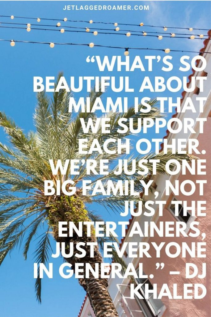 """Words from DJ Khaled """"What's so beautiful about Miami is that we support each other. We're just one big family, not just the entertainers, just everyone in general."""" in the background a sunny blue sky in Miami and pink art deco architecture building."""