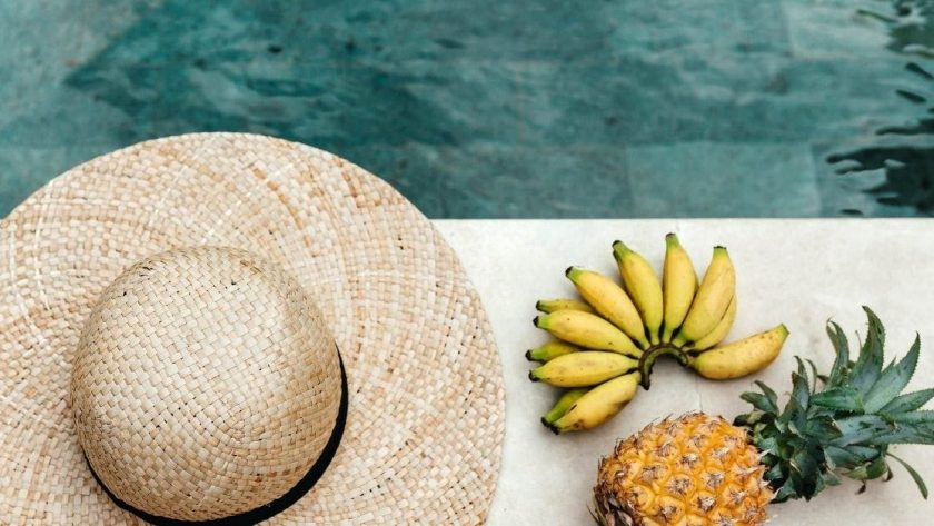 Summer captions picture of a sun hat, bananas, and a pineapple next to a clear water pool.
