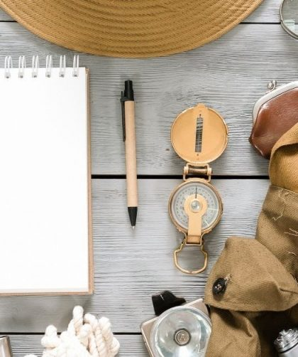 Traveling hacks photo of random travel items like a pen, notepad, and compass.