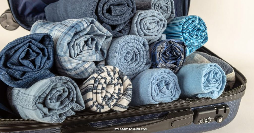 Traveling hack of a suitcase filled with rolled clothes