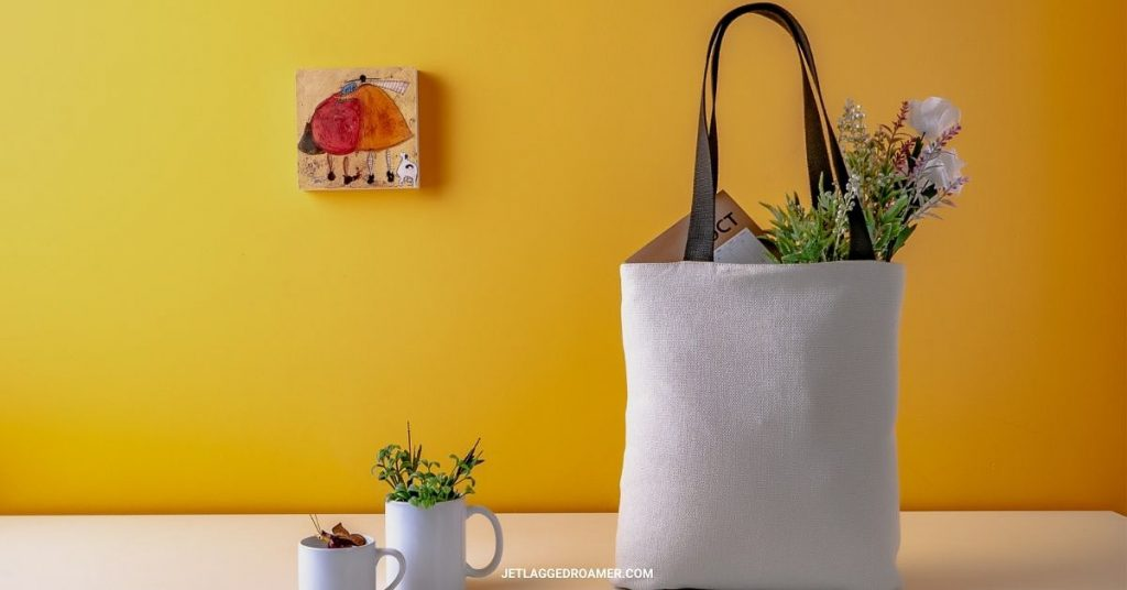 Recyclable bag filled with flowers and other groceries on a table in front of a bright yellow wall.