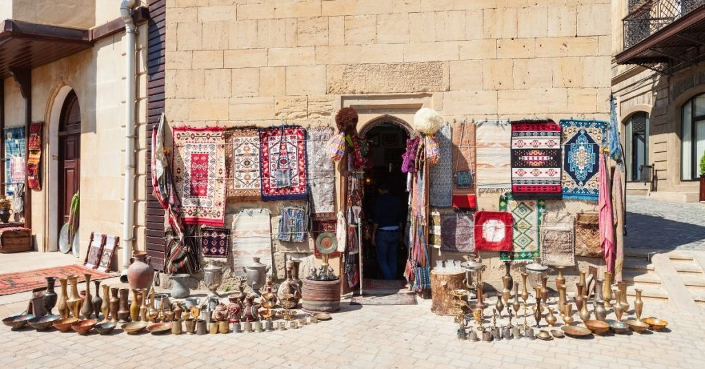 Outside of a market with a rug and other souvenirs in the middle east on a sunny day.