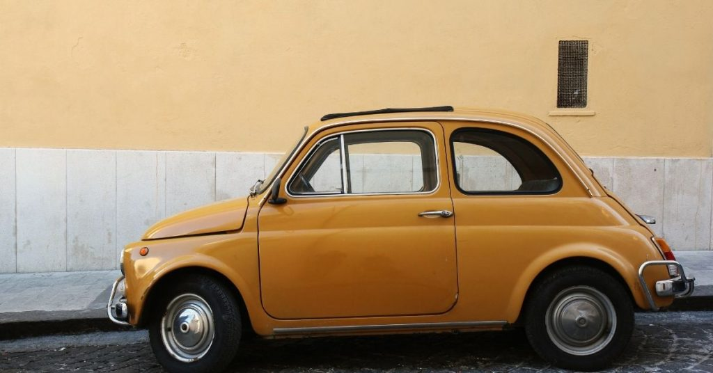 Old yell Fiat 500 parked on a charming European street.