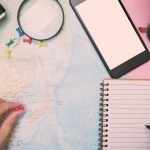 Travel expressions photo of a person looking at a map with a phone, mini notebook, and magnifying glass.