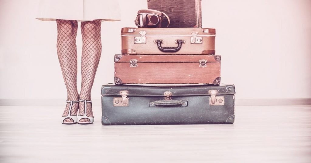 Woman dressed retro with old but stylish suitcases next to her.