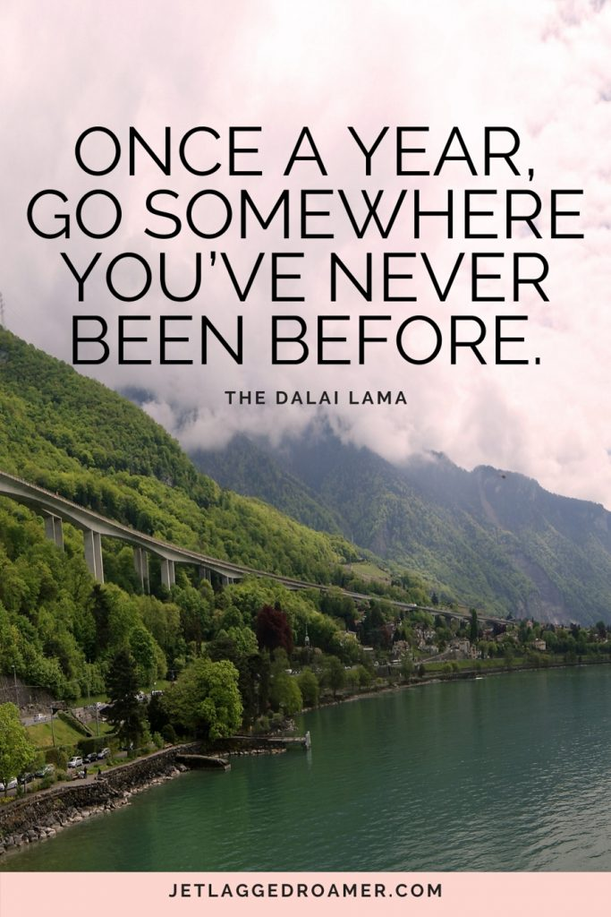 """funny travel quote that says """"Once a year, go somewhere you've never been before"""" with picture of Switzerland's green mountains and a river."""
