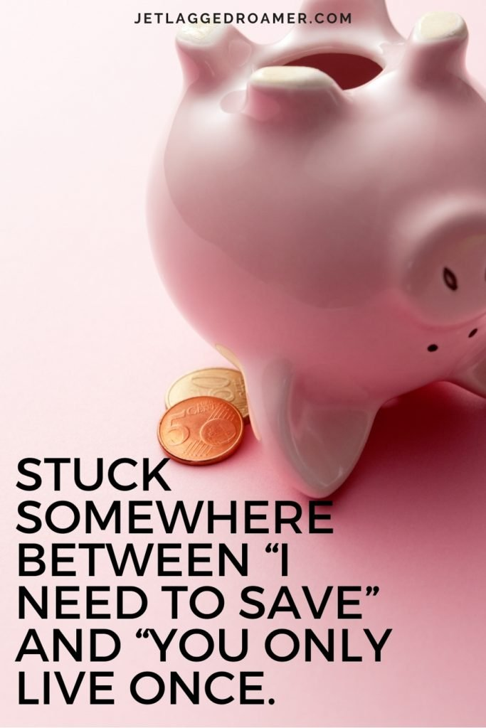 """Pink piggy bank with a few coins and funny travel quote """"Stuck somewhere between """"I need to save"""" and """"you only live once."""""""