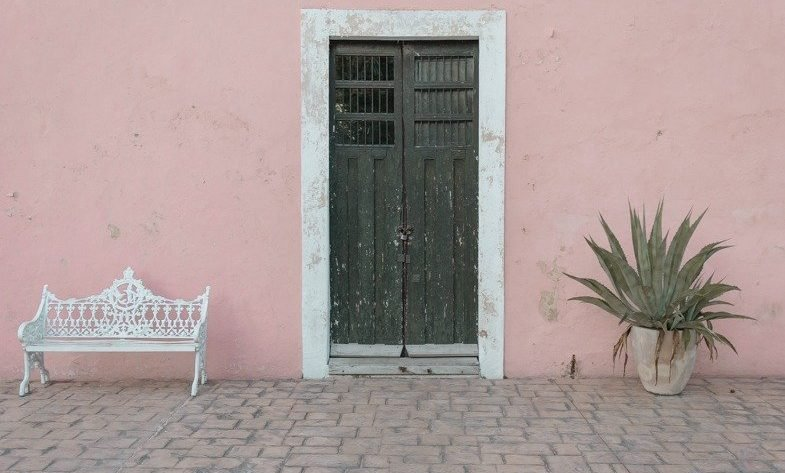 Picture of a pink building and green door in on Calzada De Los Frailes one of the top things to do in Valladolid.