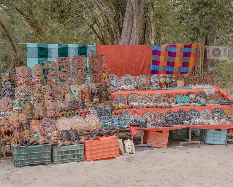 Image of a stand at Chichen Itza with Mexican blankets and souvenirs.