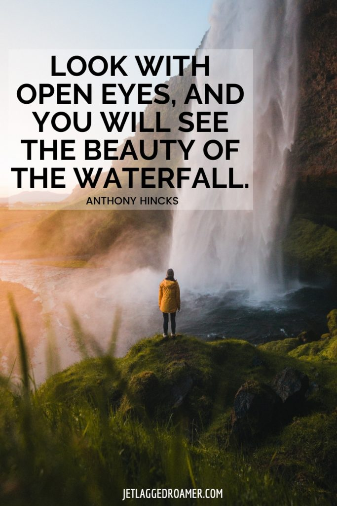 """Woman standing on a grassy knoll looking at a waterfall fall and a quote about a waterfall that says """"Look with open eyes, and you will see the beauty of the waterfall"""" by Anthony Hicks."""