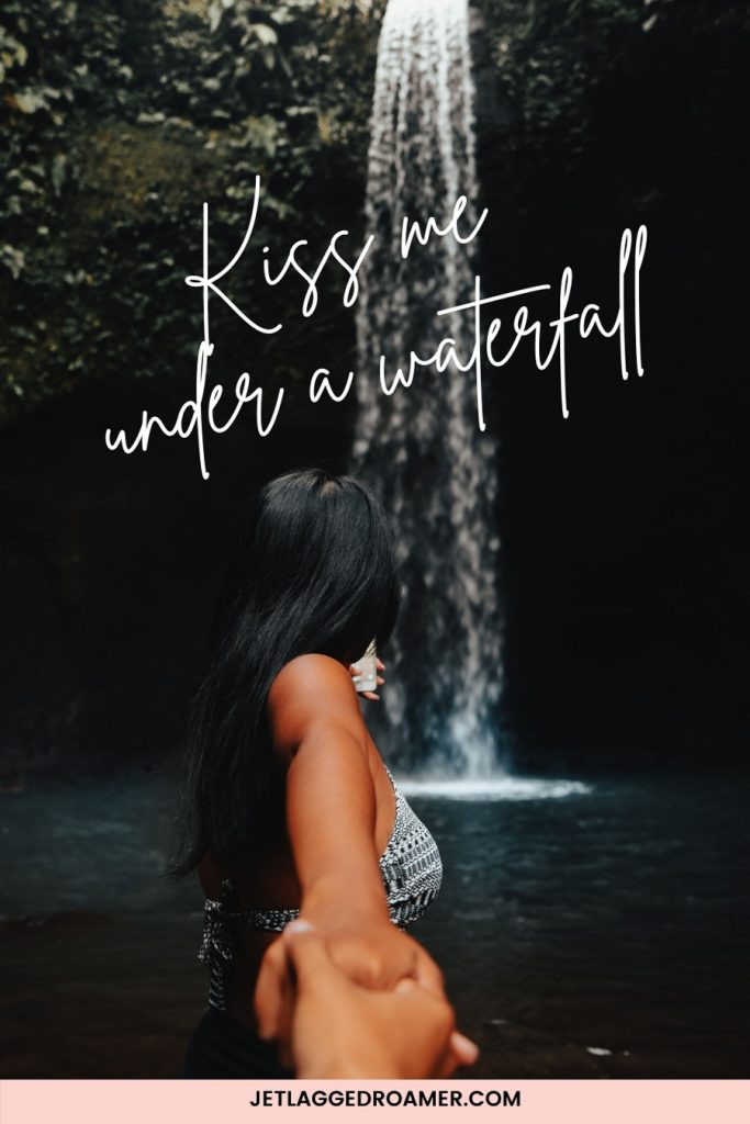 """Waterfall caption for Instagram that says """"Kiss me under a waterfall."""" Image of a woman holding someones hand and looking at a waterfall."""