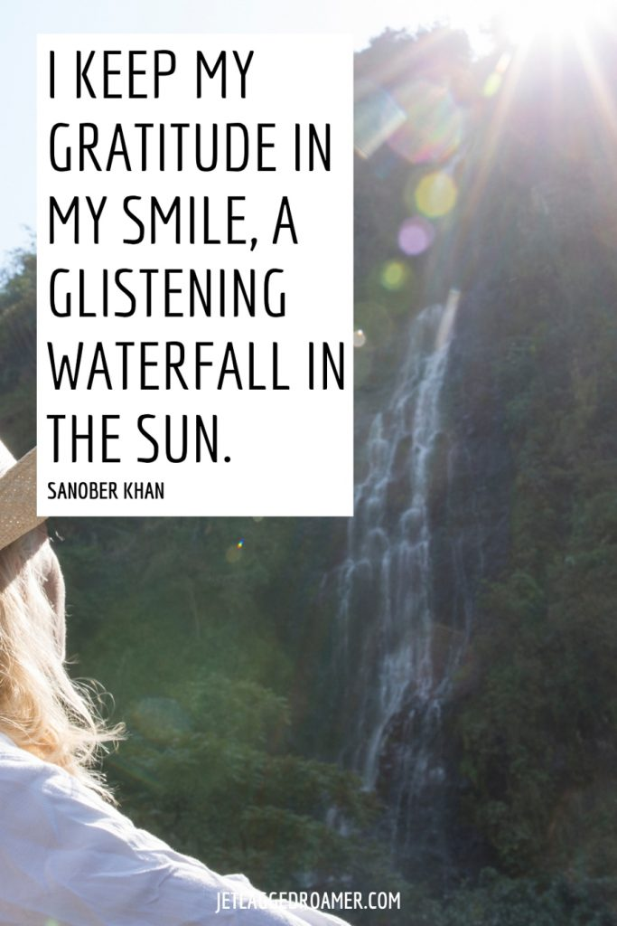 """Woman staring at a waterfall a far off on a sunny day. Text is a waterfall quote that says """"I keep my gratitude in my smile, a glistening waterfall in the sun"""" by Sanober Khan."""