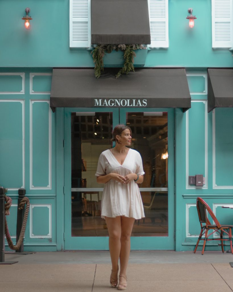 Me posing outside of Magnolias Sous Le Pont cafe, one of the cutest places to take pictures in Dallas.
