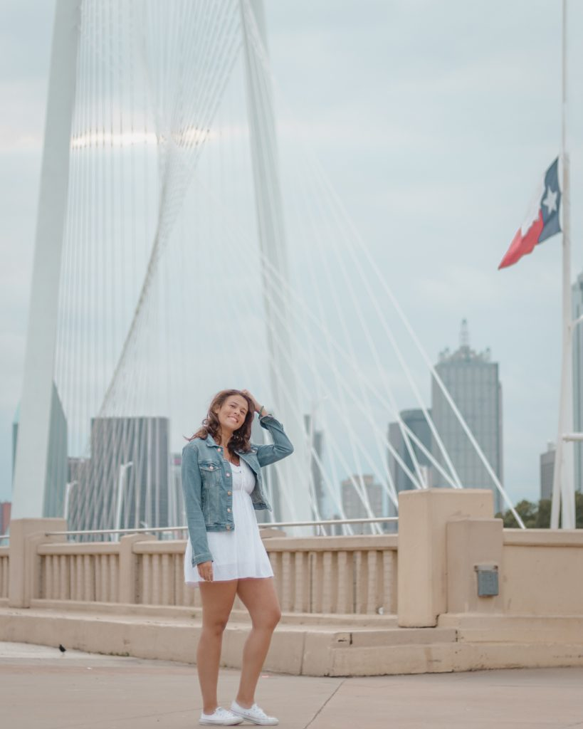Me posing in front of the Dallas skyline and Margaret Hunt Hill Bridge one of the best places to take pictures in Dallas.