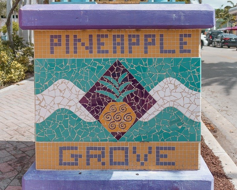 COLORFUL MOSAIC STAND THAT SAYS PINEAPPLE GROVE.