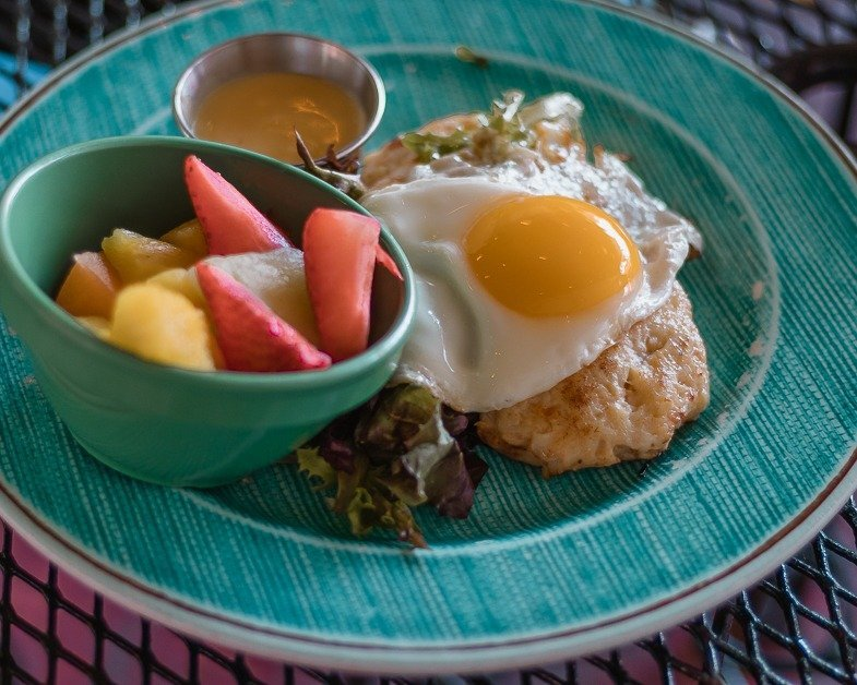 Crab cake eggs Benedict with a side of fresh fruit from Over The Bridge Cafe in Delray Beach.