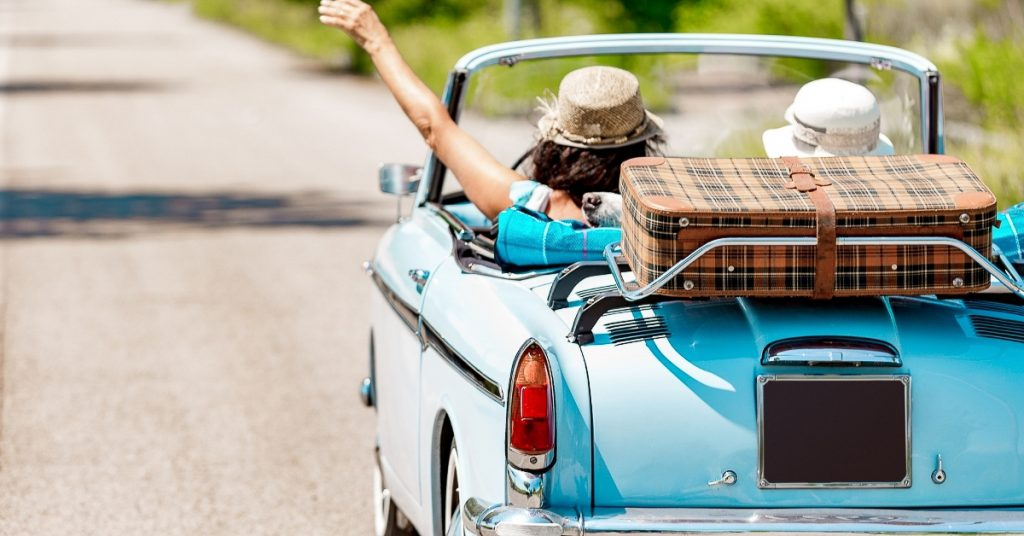 Two girlfriends driving an old convertible down a road on a sunny day.