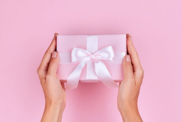 Gift for travel lovers photo os a woman holding a gift with pink wrapping paper and a white bow.